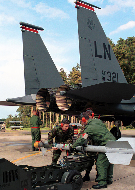 SENIOR AIRMAN (SRA), Dave Anelundi, AIRMAN First Class (A1C), Crystal Getz and STAFF Sergeant (SSGT), Clint Holman, USAF, 494th Fighter Squadron, 48th Fighter Wing (FW), Royal Air Force (RAF), Lakenheath, UK place a AIM-9 Sidewinder Missile on a MJ-1 weapons loader, after removing it from a USAF F-15 Eagle aircraft from the 48TH FW. In the background SSGT Scott Spraberry performs a routine post flight inspection of the aircraft