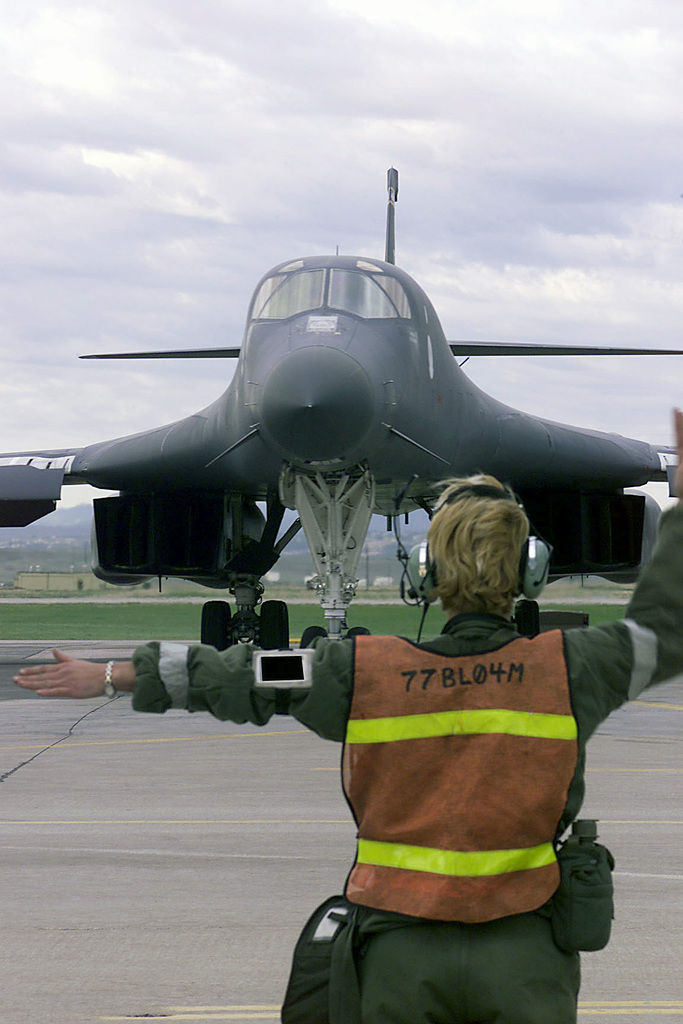 A Crewchief from the 37th Bomb Squadron, Ellsworth Air Force Base, South Dakota, guides the B-1B Lancer as it taxis out during Ellsworth's Operational Readiness Inspection