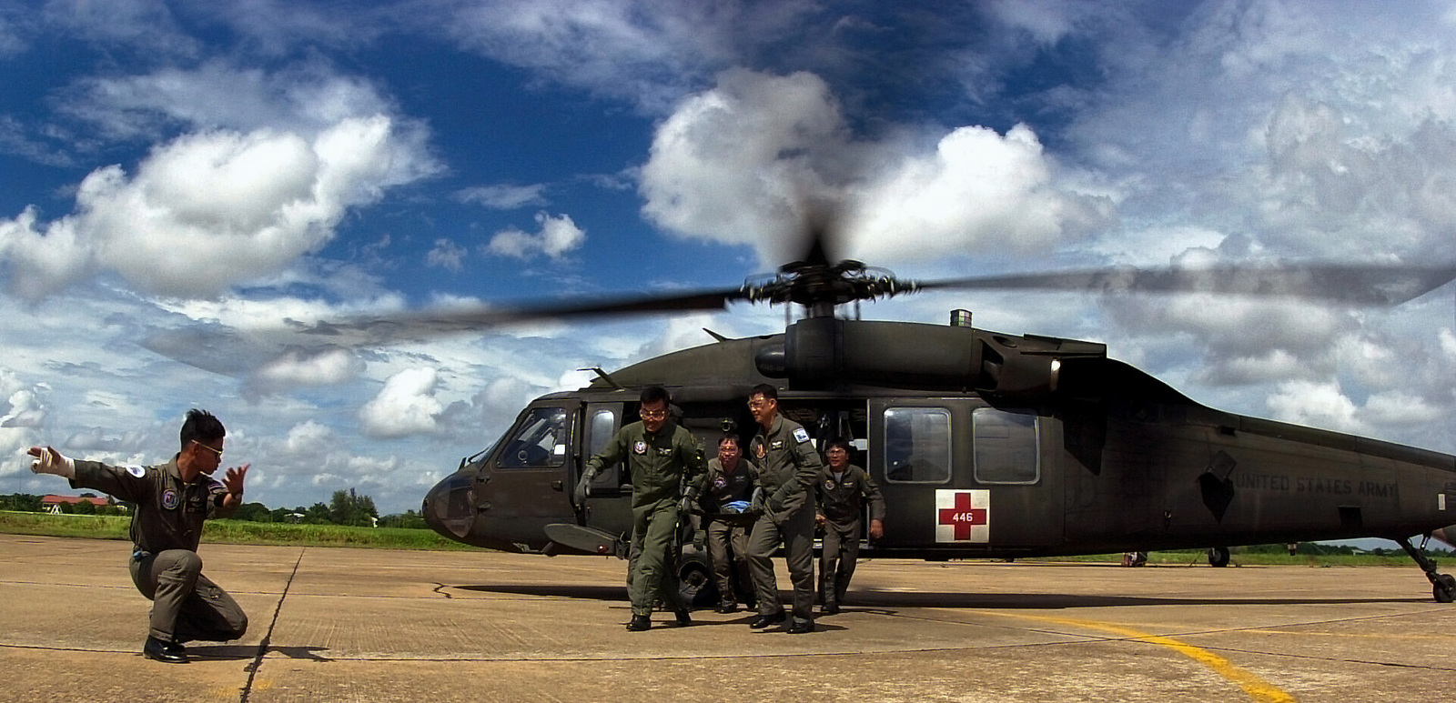 Thai medical personnel take a litter from an Army UH-60Q