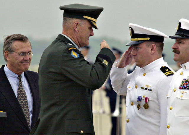 The Honorable Donald H. Rumsfeld, U.S. Secretary of Defense (left) looks on as GEN. Hugh Shelton, Chairman of the Joint Chiefs of STAFF salutes LT. Shane Osbourne, pilot of the EP-3E ARIES II which collided with a Chinese fighter jet over the South China Sea. (DoD photo by PETTY Officer 2nd Class Bob Haulihan) (Released)