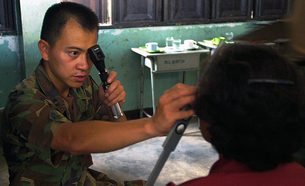 United States Army Captain James Truong, Optometrist, Tripler Medical Center, Hawaii, checks a Thai patients vision. CAPT. Truong is part of a combined U.S. and Thai medical team sent out to provide medical aid and patient care to local farm communities in support of the COBRA GOLD 2001 exercise. COBRA GOLD 2001 is a regularly scheduled, joint exercise designed to ensure regional peace and strengthen the ability of the royal Thai Armed Forces to defend Thailand or respond to regional contingencies. This year's exercise is the 20th such exercise