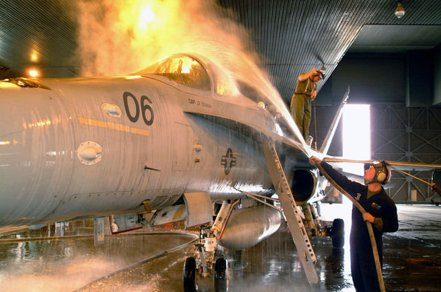 "Marine Corporal (CPL) Daniel King, sprays down an FA-18 ""Hornet"" fighter aircraft, in a wash hanger at Misawa Air Base, Japan"