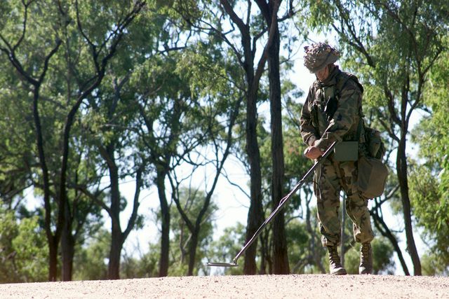 Using a AN/PSS-12 Metallic Mine Detector, Lance Corporal Sean Peterson, Combat Support Company, 3rd Battalion, 3rd Marine Regiment, uses a sweeping motion to cover large areas of ground as he searches for enemy mines during Exercise TANDEM THRUST 2001. TANDEM THRUST is a biannual combined United States and Australian military training exercise held in Shoalwater Bay training area, Queensland, Australia