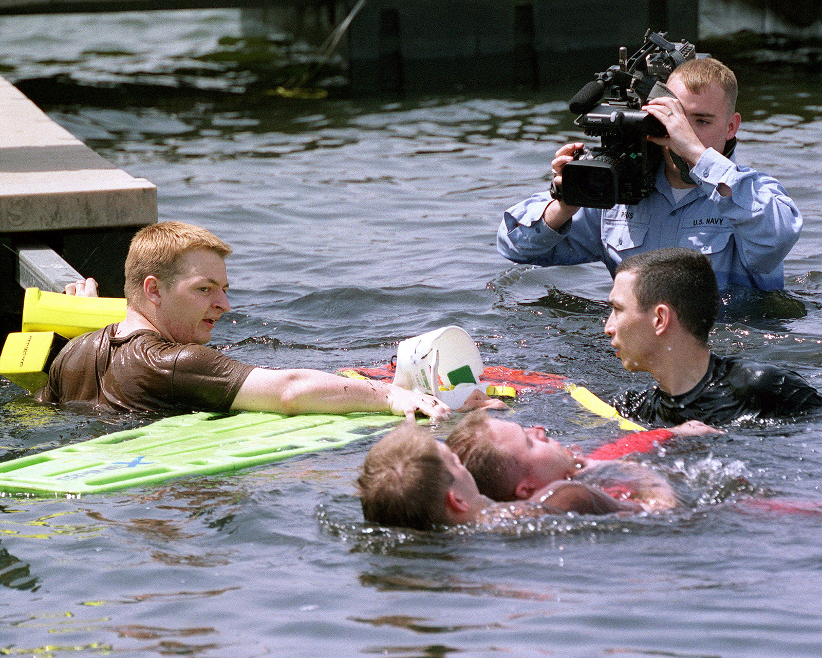 """Navy Journalist 3rd Class (JO3) Jack Rous videotapes United States Air Force (USAF) SENIOR AIRMAN (SRA) Brad Starkey and STAFF Sergeant (SSGT) Albert Hopkins during the water-rescue portion of the """"6th Annual Emergency Medical Technicians Rodeo"""" held at Misawa Air Base, Japan"""