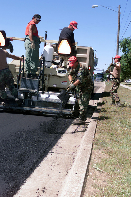 STAFF Sergeant (SSGT) William Brown, 202 Red Horse Civil Engineer Squadron reserve unit from Camp Blanding Florida, uses a shovel to clear the gutter of any excess asphalt while civilian Tom Harris, (left), 27th Civil Engineer Squadron Cannon AFB watches his progress. SSGT Jim Maloney, USAF, pilots the Ingersoll Rand 650P Crawler Asphalt Paver