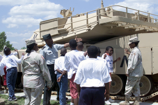 """Major (MAJ) Tim Goff (center) US Army (USA), USA Forces Command (FORCSOM), Sergeant (SGT) Kristal Kuehnel and SGT Nilsa Tolbert, USA FORSCOM brief students from the """"Little Soldiers from Dean Rusk Elementary School"""" on the USA M1A1 Abrams Main Battle Tank (MBT). The soldiers are participating in a FORSCOM and United Way Organization sponsored, Partners in Education Program"""