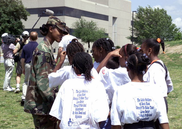 """MASTER Sergeant (MSG) Carolina Johnson, US Army (USA), Forces Command (FORSCOM), talks with her group of girls from the """"Little Soldiers from Dean Rusk Elementary School"""". MSG Johnson is participating in a FORSCOM sponsored Partners in Education Program and a video crew from The United Way Organization is at the school to film interaction between the groups"""