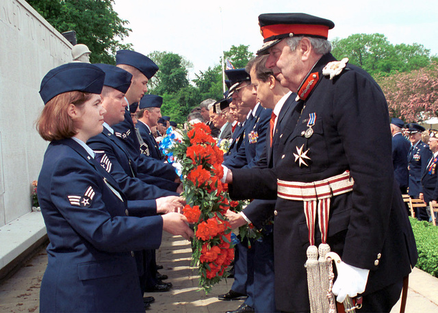 "During the Madingley Memorial Day Commemorative Services held at Cambridge American Military Cemetery, Coton, Cambridge, UK, USAF personnel assigned to the 48TH Fighter Wing, Royal Air Force, Lakenheath, UK pass the traditional flower wreaths to the Presenters during the Ceremony. The presenters will then lay their wreath on the ""Wall of the Missing"" to honor the men and women buried at Cambridge American Military Cemetery, and those whose names are engraved on the Wall. The cemetery was dedicated on July 16, 1956, as the only permanent American World War II cemetery in the British Isles"