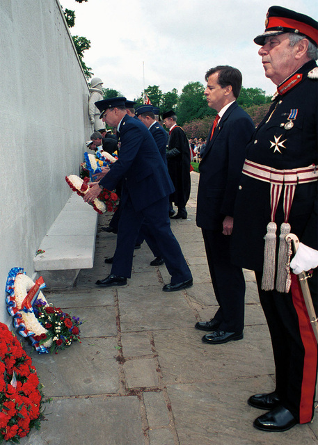 Her Majesty's Lord Lieutenant of Cambridgeshire, Mr. James Crowden and Mr. Glyn Davies, charge D' Affaires of the United States Embassy in London wait while General Gregory S. Martin the commander, US Air Forces in Europe, Ramstein Air Base, Germany and other presenters place their wreaths on the Wall of the Missing during the Madingley Memorial Day Commemorative Service. The wreaths are placed on the wall to honor the men and women buried at Cambridge American Military Cemetery, and whose names are engraved on the Wall of the Missing. The ceremony was held at Cambridge American Military Cemetery, Coton, Cambridge, United Kingdom