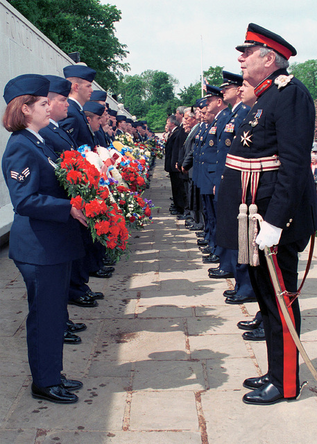 (Left) Members of the 48th Fighter Wing, RAF Lakenheath, United Kingdom, and Junior Reserve Officer Training Corp (JROTC) from Lakenheath High School prepare to hand the wreath to the (Right) presenters during Madingley Memorial Day Commemorative Service. The presenters will then lay their wreath on the Wall of the Missing to honor the men and women buried at Cambridge American Military Cemetery, and those who's names are engraved on the Wall of the Missing at the Madingley Memorial Day Commemorative Service. The ceremony was held at Cambridge American Military Cemetery, Coton, Cambridge, United Kingdom