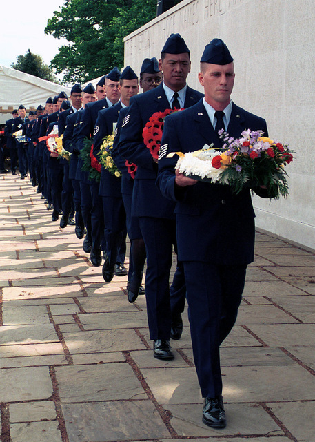 Members of the 48th Fighter Wing, Royal Air Force Lakenheath, United Kingdom, and Junior Reserve Officer Training Corps from Lakenheath High School carry floral wreaths. The floral wreaths will be given to presenters who will lay them on the Wall of the Missing to honor the men and women buried, and those who's names are engraved on the Wall of the Missing at the Madingley Memorial Day Commemorative Service. The ceremony was held at Cambridge American Cemetery, Coton, Cambridge, United Kingdom