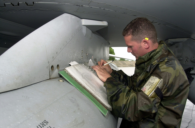 Making annotations in an aircraft log, US Air Force SENIOR AIRMAN Jason Via, 555th Fighter Squadron, Aviano Air Base, Italy, performs post-flight checks on an F-16 Fighting Falcon aircraft after arrival at Malacky Air Base, Republic of Slovakia, for a Weapons Training Deployment. The range at Malacky allows the 555th Fighter Squadron to maintain proficiency and accuracy in armament delivery
