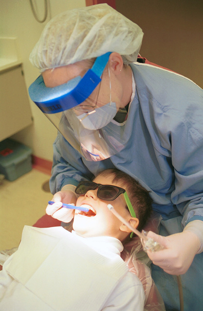 AIRMAN 1ST Class Shelby Anderson cleans 7-year old Robert Birrenbach's teeth during his annual check-up. Anderson is a dental apprentice with the 48th Dental Squadron, assigned to the 48th Medical Group, RAF Lakenheath, United Kingdom