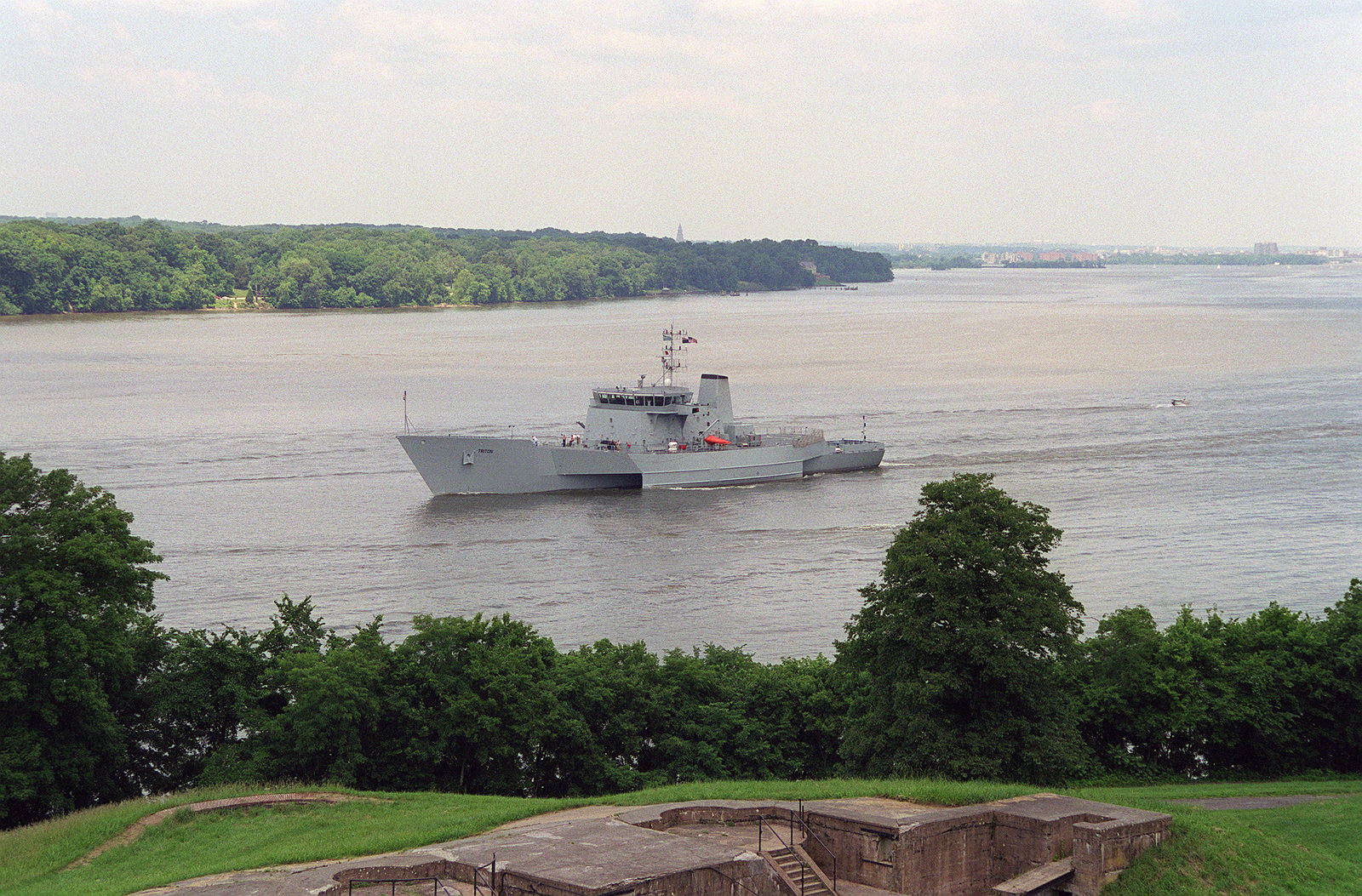 Port bow view of the United Kingdom research vessel RV TRITON passing under the ramparts of historic Fort Washington. The vessel is sailing down river after completing a port visit to the Washington District of Columbia area