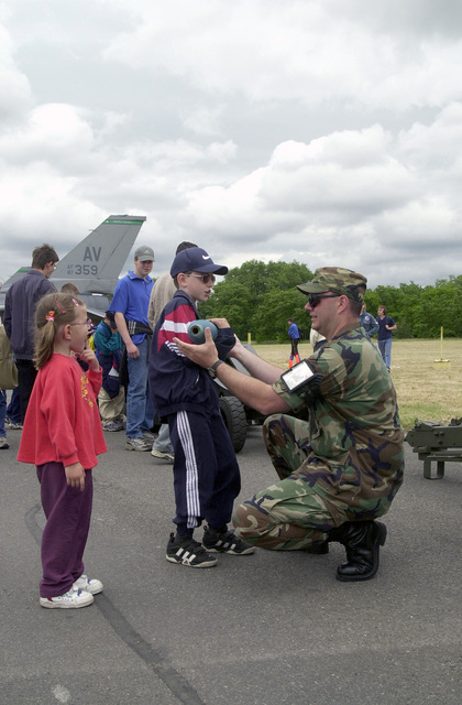 US Air Force STAFF Sergeant Scott Straley, 31st Maintenance Squadron, Aviano Air Base, Italy, shows two Slovakian youths a BDU-33 practice munition at an open house display at Malacky Air Base, Republic of Slovakia