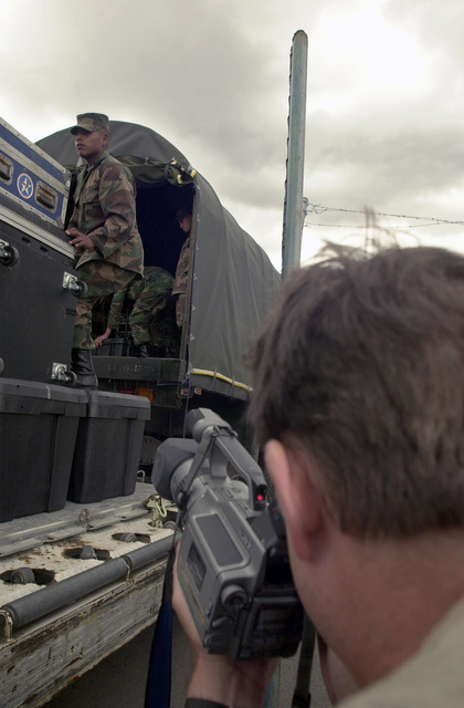 Mr. Kim B. Pardue, US Army South Training Support Center, Videographer, documents footage of Ecuadorian Army soldiers loading equipment onto a truck at the Military Airport at Quito Ecuador, in support of Peacekeeping Operations (PKO) South 2001