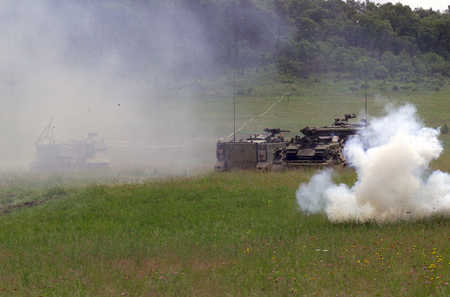 An explosive device is used to simulate the detonation of an M62A2 Inert Linear Demolition Charge, as soldiers aboard an M113 Armored Personnel Carrier (APC) and an M88A1 Armored Recovery Vehicle wait to move out, at the Multiple Purpose Training Range, at Fort McCoy, Wisconsin