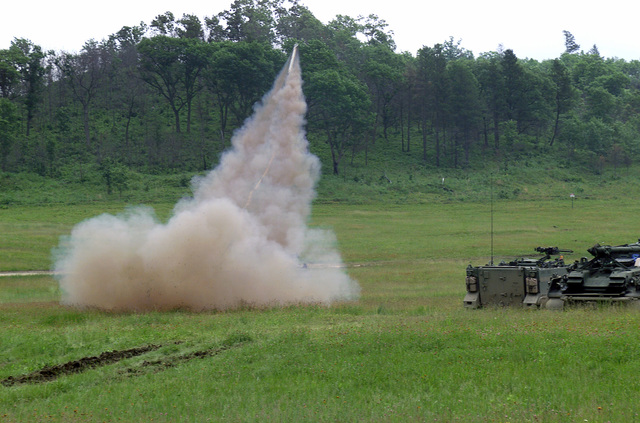 An M62A2 Inert Linear Demolition Charge is ground launched at the Multiple Purpose Training Range, at Fort McCoy, Wisconsin with an M113 Armored Personnel Carrier (APC) and an M88A1 Armored Recovery Vehicle parked near by