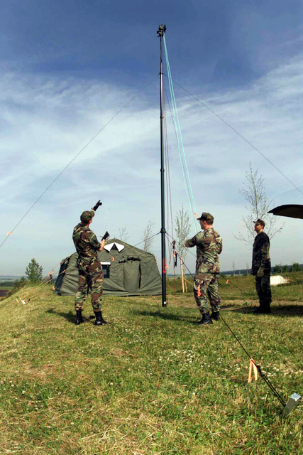 (right to left) US Air Force Technical Sergeant Andrew Pryor, US Air Force AIRMAN First Class William Mckowan, and US Air Force STAFF Sergeant Mark Hiers, 52nd Communications Squadron, Air Expeditionary Communications Package team members adjust a microwave antenna at a relay station during a local communications exercise at Spangdahlem Air Base, Germany. Microwave shots give the ability to extend communications services to users at greater distances without running cable