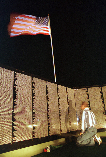 The Moving Wall, or Vietnam Veterans Memorial replica at night with a visitor studying the names inscribed and the American flag waving above, at Travis Air Force Base, California