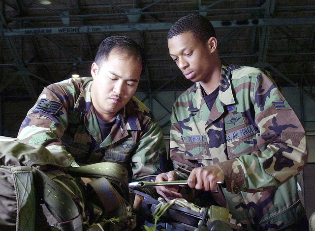 "Technical Sergeant (TSGT) Robin Olaes, USAF, (left), and AIRMAN First Class (A1C) Mike Powell, USAF, air transportation specialists, 374th Transportation Squadron/Combat Mobility Element (CME), Yokota Air Base, Japan, inspect Type V platforms for wear and tear prior to an airdrop mission. These are used for Pacific Air Force unilateral ""low velocity heavy platform"" airdrop training"