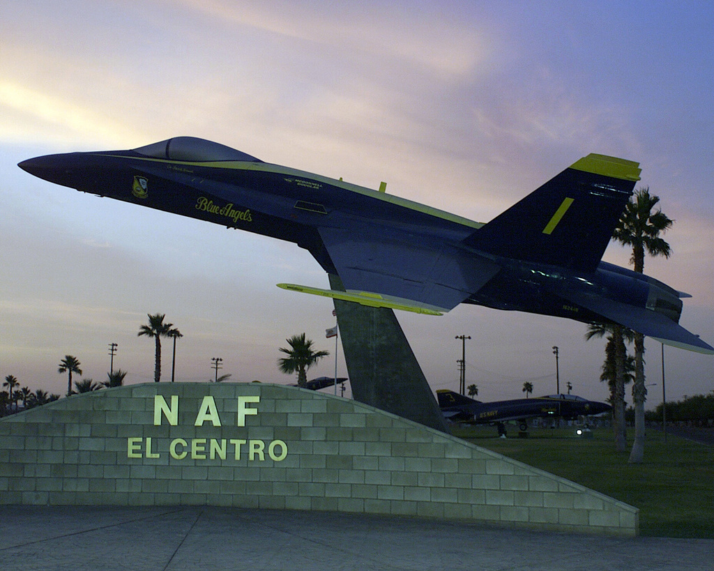 At the entrance to Naval Air Field El Centro, mounted on a pillar, an F-18 Hornet from the Blue Angels Squadron is silhouetted against the desert sunset