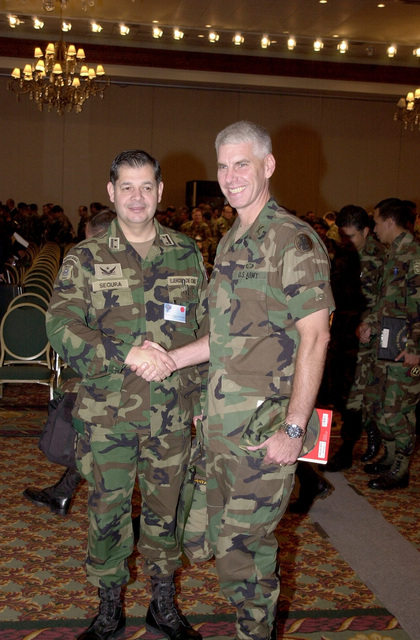 US Army Colonel (COL) Jeffery T. Christiansen, US Army South, Deputy Commander for Operations, Co-Director for United Forces Peacekeeping Operations South-01, shakes hands with Chilean COL Valentin Segura at the opening ceremony in Quito, Ecuador. The peacekeeping exercise is a series of multi-national interacive seminars