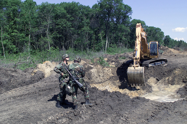 Brigadier General (BGEN) Michael Jelinsky (left), USA, Deputy Commander 88th Regional Support Command, talks with First Lieutenant (1LT) Malcolm USA, Headquarters Headquarters Company, 863rd Engineer Battalion, as a tracked backhoe digs an excavation pit for a new road at the Multiple Purpose Training Range, at Fort McCoy, Wisconsin. 1LT Malcolm is armed with a 5.56mm M16A2 assault rifle