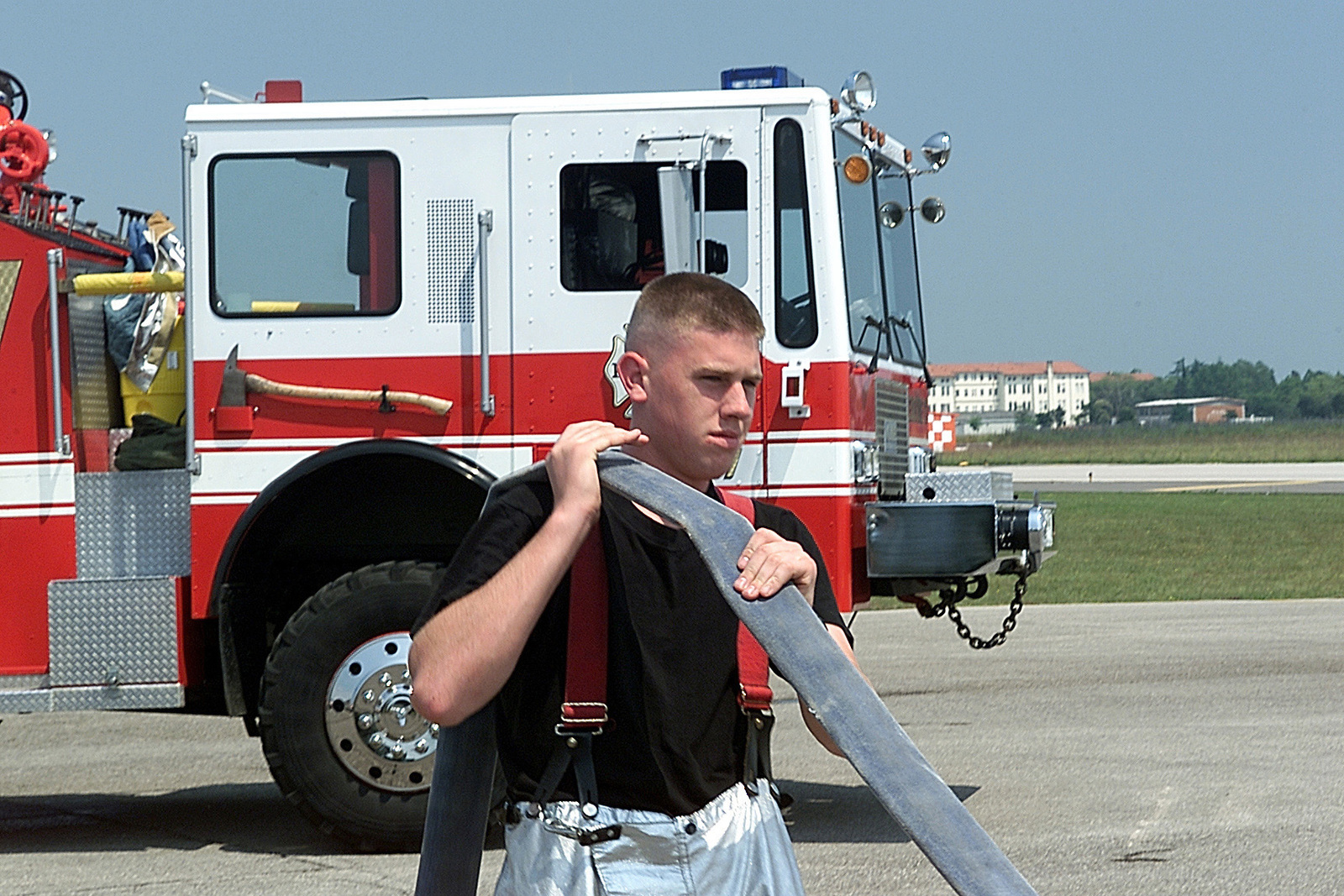 AIRMAN (AMN), James Burke, USAF, Fire Protection Specialists, 31ST Civil Engineer Squadron, Fire Protection Flight, walks the water out of a fire hose before loading it onto the P-24 Structural Pumper Fire Truck during a fire fighters training course at Aviano AB, Italy