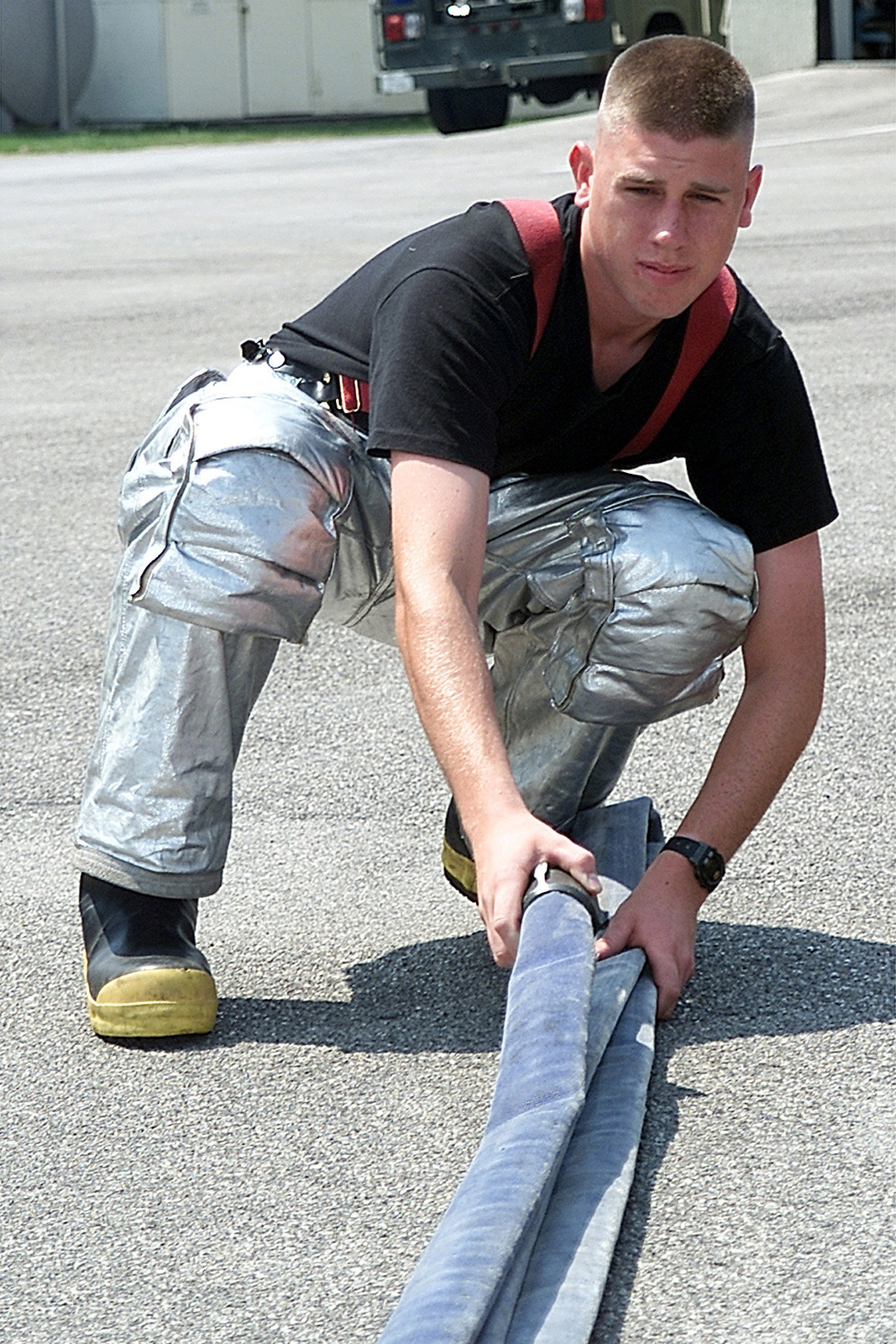 AIRMAN (AMN), James Burke, USAF, Fire Protection Specialists, 31ST Civil Engineer Squadron, Fire Protection Flight, prepares a fire hose for reloading after a fire fighters training course at Aviano AB, Italy