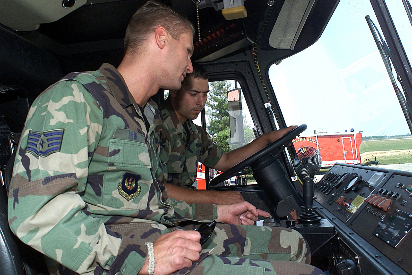 STAFF Sergeant (SSGT), Paul Hine, USAF, Fire Protection SPECIALIST, 31ST Civil Engineer Squadron (CES), Fire Protection Flight, Aviano AB, Italy, instructs AIRMAN First Class (A1C), Matthew Haire, on the operation of the bumper and roof water turret, on the P-23 Airport and Rescue Fire Fighting Vehicle, during a training course at Aviano AB, Italy
