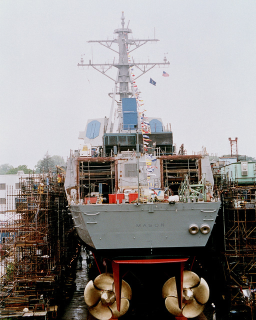 Direct stern-on view of the Arleigh Burke class Aegis guided missile destroyer USS MASON (DDG 87) resting on the launch ways shortly before her christening at the Bath Iron Works Shipyard. The ships large bronze screws are visible in the view. This is the last Navy ship to be launched down the traditional inclined way