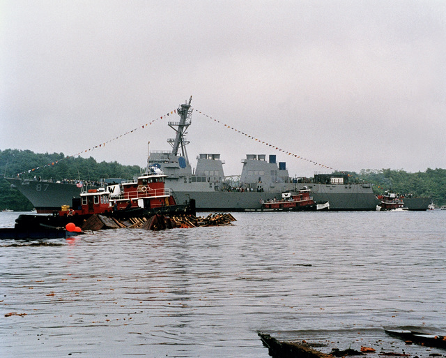 Port side view of the Arleigh Burke class Aegis guided missile destroyer USS MASON (DDG 87) waterborne in the Kennebec River following the ships christening and launch ceremony. To the left, tug boats gather up the remains of the launch cradle. This is the last Navy vessel to be slid down the ways in the traditional manner