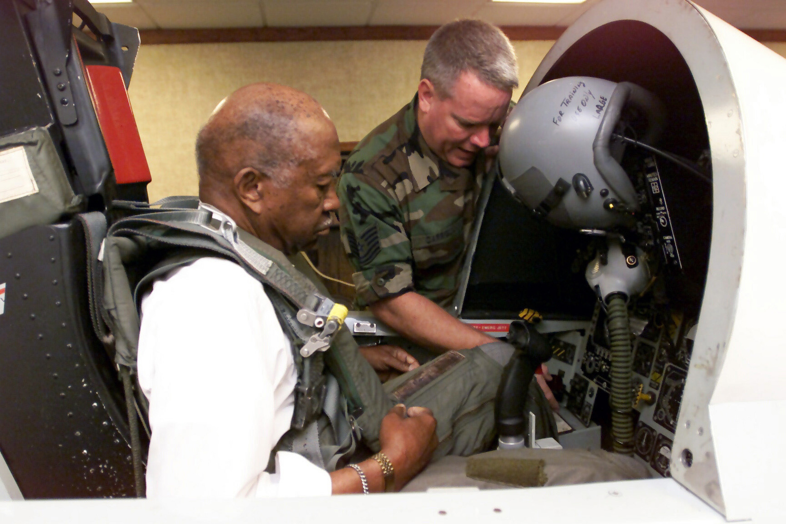 Technical Sergeant Patrick Carroll, right, 1ST Fighter Wing SERE (Survival, Evasion, Resistance, and Escape) SPECIALIST, demonstrates how to adjust the rudder pedals in the F-15 egress simulator to Lieutenant Colonel (ret) Francis Horne prior to his F-15 flight at Langley Air Force Base, Virginia. Horne is one of the original Tuskegee AIRMAN