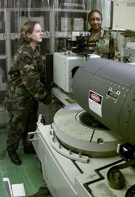 SENIOR AIRMAN Jocelyn Burrowes, right, and AIRMAN first Class Jennifer Hanaway, left, Avionics Sensors Technicians assigned to the 31st Maintenance Squadron, Avionics Flight, Aviano AB, Italy; perform laser targeting tracking adjustments on a Low Altitude Navigational Targeting Infra-Red for Night system pod (LANTIRN). The LANTIRN pod controls all laser guided munitions and navigational systems during night flying operations on many different airframes, this pod is set to operate on Aviano's F-16 Vipers