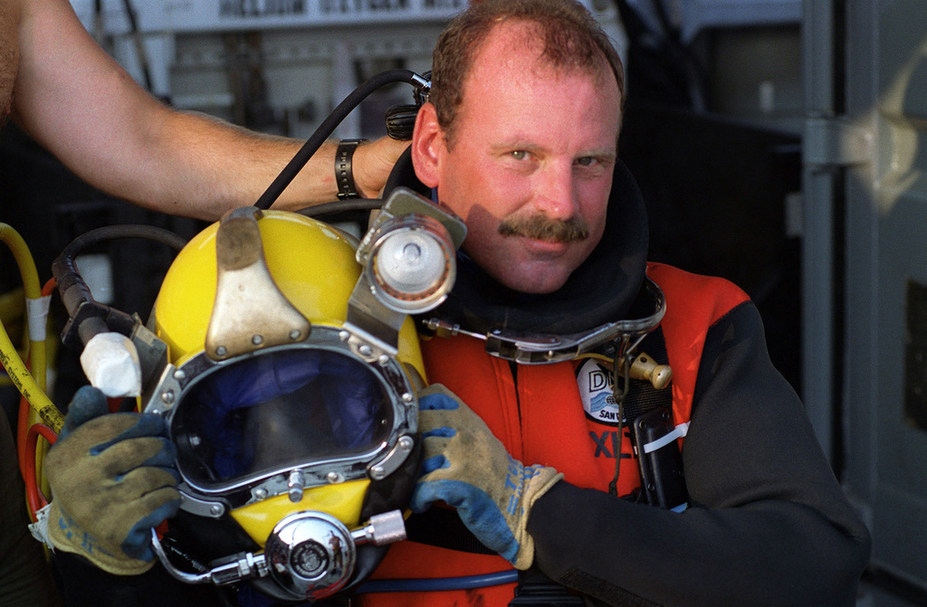 US Navy (USN) CHIEF Hospital Corpsman (HMC) Mike Cockrill, Mobile Diving and Salvage Unit Two (MDSU-2), holds his MK 21 Mod One diving helmet, as the prepares for a dive, onboard the Derrick Barge, WOTAN, during Phase II of the Monitor 2001 Expedition