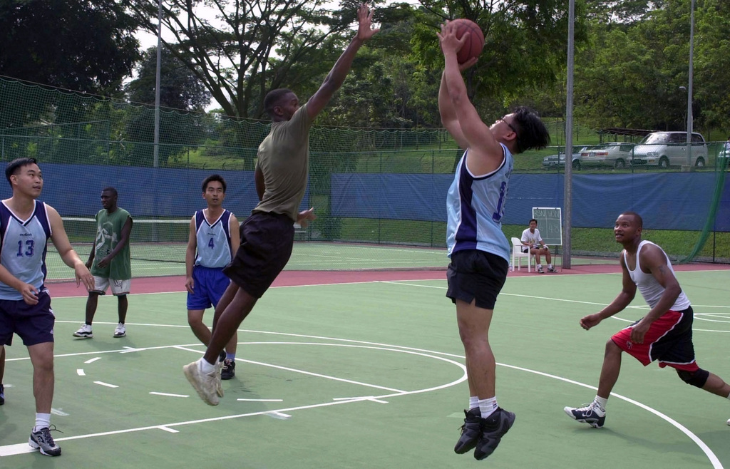 United States Navy and Republic of Singapore Sailors participate in a spirited basketball game at the Terror Club in Singapore, on July 4th