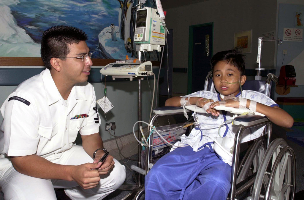 Musician Second Class (MU2) Jeremy Bustillos, from Irving, Texas, with the United States Navy (USN) Seventh Fleet Band, Yokosuka, Japan, talks to Firdaus Twa, at the KK Women's and Children's Hospital in Singapore, during the seventh annual Cooperation Afloat Readiness and Training (CARAT) 2001 exercise