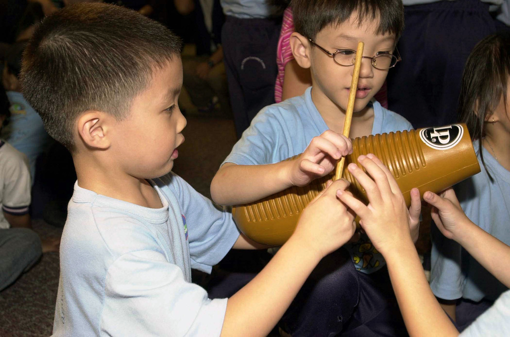 Twong Tae (left) and Swa Mong, examine a percussion instrument at the KK Women's and Children's Hospital in Singapore, during a benefit concert conducted by the United States Navy (USN) Seventh Fleet Band, stationed in Yokosuka, Japan, during the seventh annual Cooperation Afloat Readiness and Training (CARAT) 2001 exercise