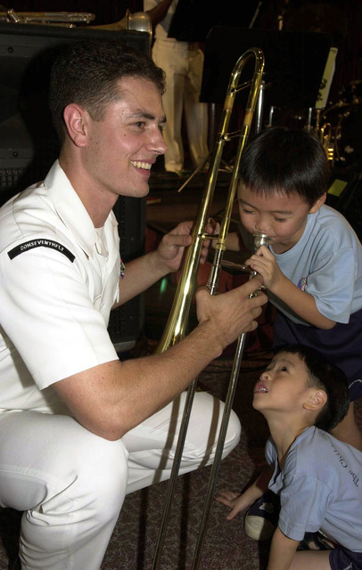 United States Navy (USN) Seventh Fleet Band member, Musician Third Class (MU3) Jeremiah Garwick, from Eagle River, Alaska, stationed at Yokosuka, Japan, entertains young music enthusiasts at the KK Women's and Children's Hospital in Singapore, during the seventh annual Cooperation Afloat Readiness and Training (CARAT) 2001 exercise