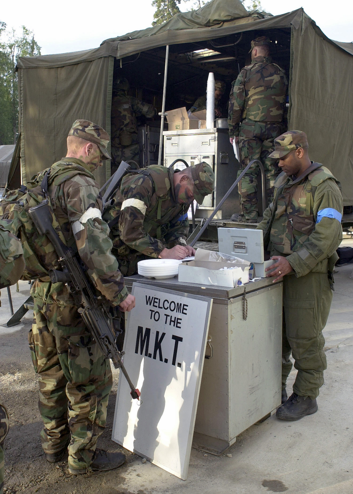 STAFF Sergeant Michael Harris (r), 3rd Services Squadron, Elmendorf AFB, collects money from Security Forces troops prior to breakfast at the Mobile Kitchen Trailer on Camp Mad Bull
