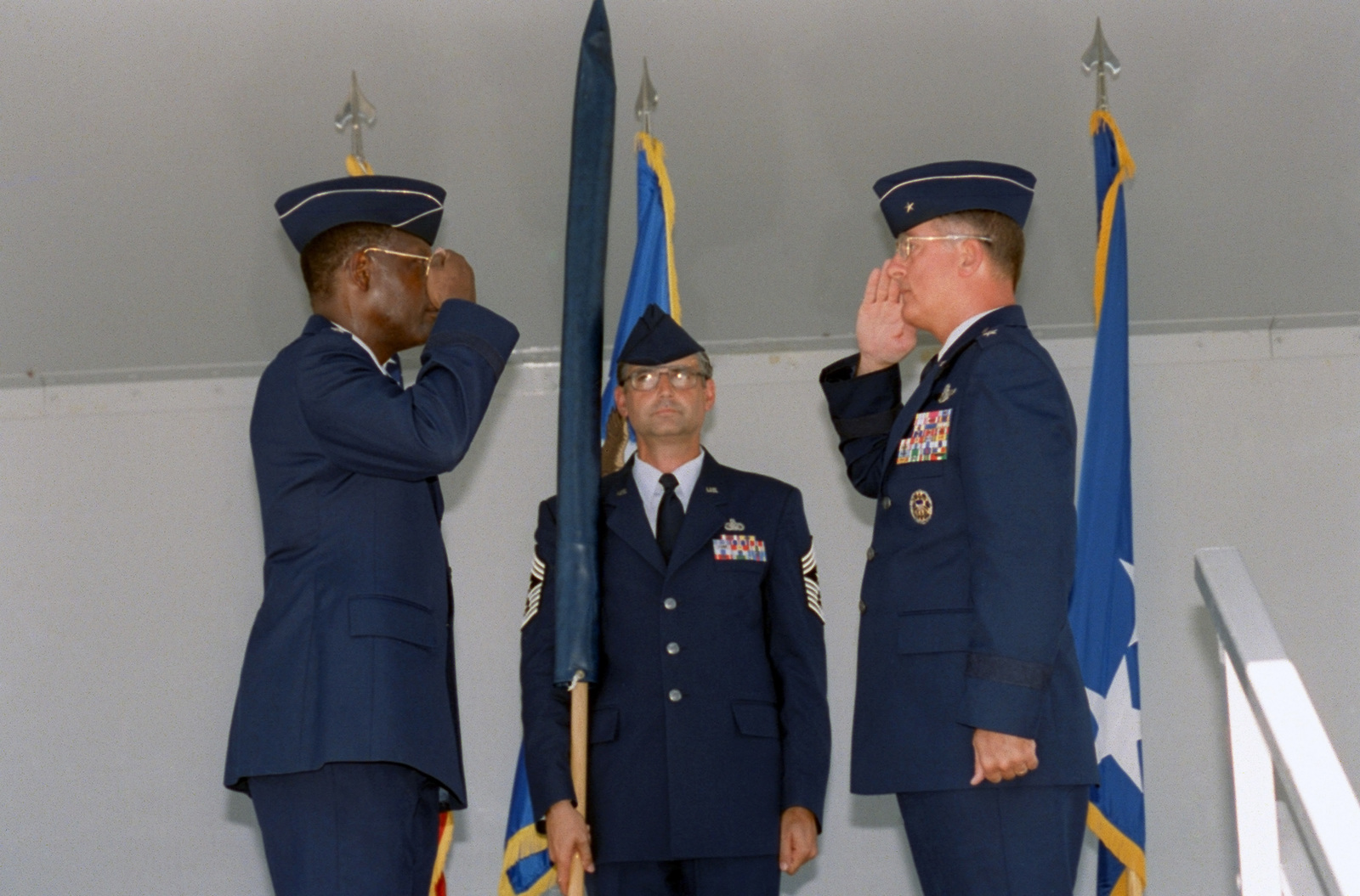 Brigadier General (BGEN) Robert Murdock, (right), USAF, San Antonio - Air Logistics Center (SA-ALC) Commander, relinquishes command to General (GEN) Lester L. Lyles, (left), USAF, Commander, Air Force Material Command (AFMC). CHIEF MASTER Sergeant (CMSGT) BIll Schuster, SA-ALC Command CHIEF holds agency's guidon, during the Kelly AFB closing ceremonies. Although the closing ceremony is in history books, government officials still actually own Kelly property and will until federal and state environmental regulators okay remedies for the installation's 30 sites that need environmental clean-up, according to federal law provisions