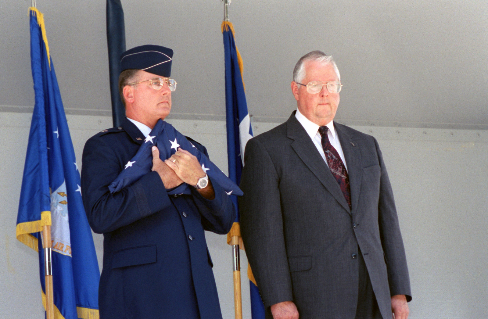 Brigadier General (BGEN) Robert Murdock, USAF, San Antonio - Air Logistics Center (SA-ALC) Commander, holds the last American flag to fly over Kelly AFB, and Tommy Jordan Executive Director SA-ALC stands on his left, during the closing ceremonies. Although the closing ceremony is in history books, government officials still actually own Kelly property and will until federal and state environmental regulators okay remedies for the installation's 30 sites that need environmental clean-up, according to federal law provisions