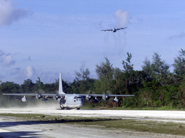 C-130 Hercules turboprop aircraft from VMGR-152, 1ST Marine Air Wing, Okinawa, Japan, lands on the island of Peleliu as another C-130 from the same unit flies above during Exercise KOA THUNDER 2001. Marines from Aviation Support Element, Kaneohe Bay, Hawaii, 1ST Marine Air Wing, Okinawa, Japan, and 3rd Marines 7th Battalion, 29 Palms, California, participated in KOA THUNDER on the island of Guam from July 9 to July 14. The purpose of the exercise was to demonstrate the Marine Corps ability to deploy in the South Pacific from places other than Okinawa, Japan
