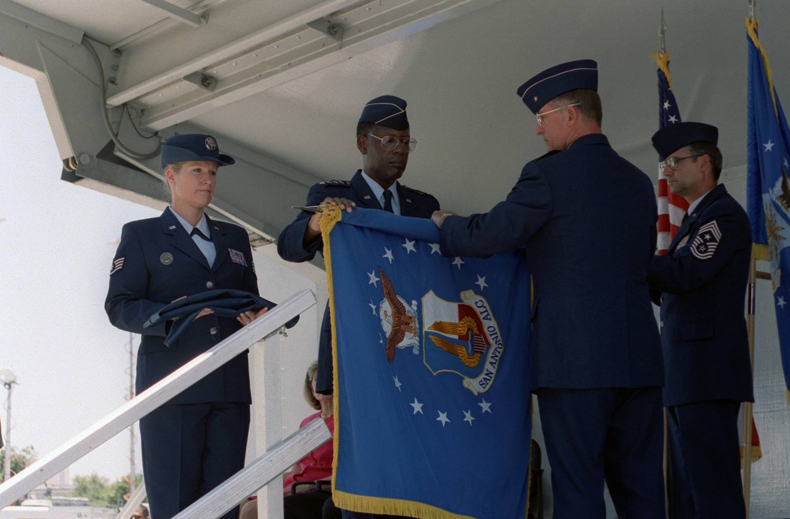 General (GEN) Lester L. Lyles, (left), USAF, Commander, Air Force Material Command (AFMC), and Brigadier General (BGEN) Robert Murdock, USAF, San Antonio - Air Logistics Center (SA-ALC) Commander, roll up the agency's guidon in preparation to case it, during the Kelly AFB closing ceremonies. Although the closing ceremony is in history books, government officials still actually own Kelly property and will until federal and state environmental regulators okay remedies for the installation's 30 sites that need environmental clean-up, according to federal law provisions