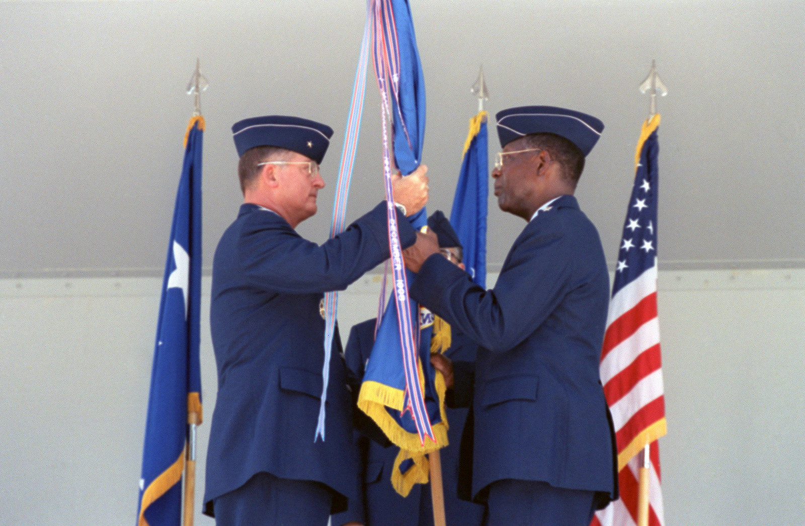 General (GEN) Lester L. Lyles, (right), USAF, Commander, Air Force Material Command (AFMC), receives the Kelly AFB, Guidon from Brigadier General (BGEN) Robert Murdock, USAF, San Antonio - Air Logistics Center (SA-ALC) Commander, during the bases closing ceremonies. Although the closing ceremony is in history books, government officials still actually own Kelly property and will until federal and state environmental regulators okay remedies for the installation's 30 sites that need environmental clean-up, according to federal law provisions