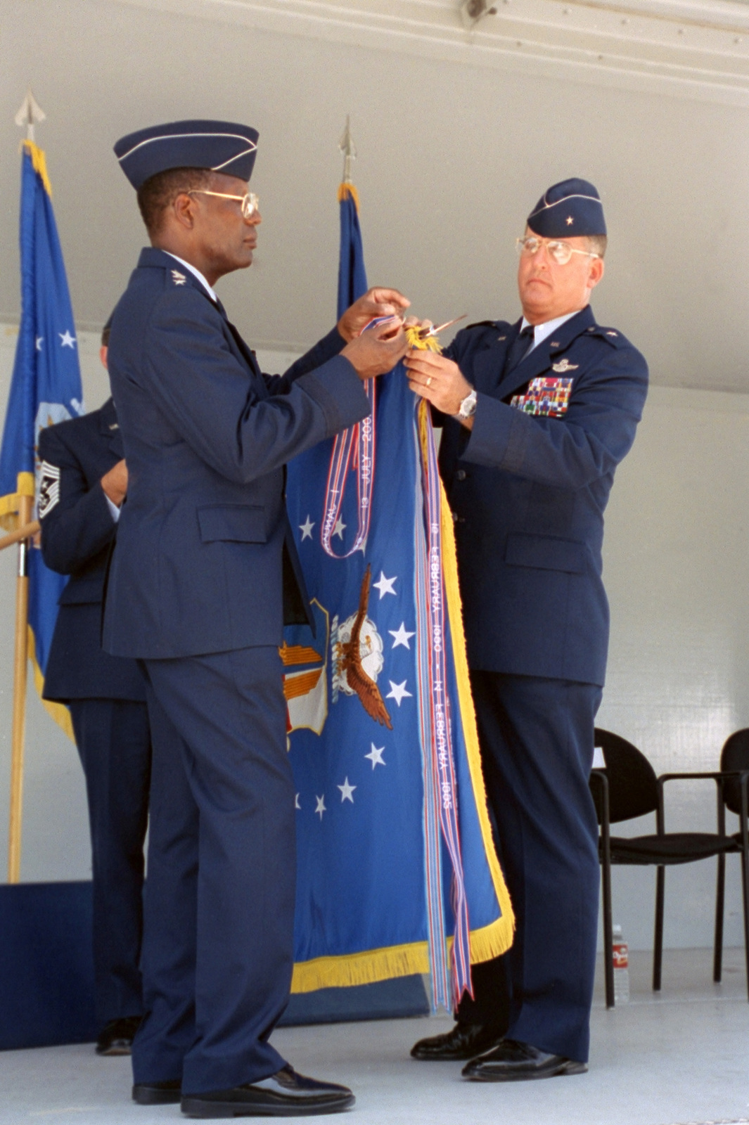 General (GEN) Lester L. Lyles, USAF, Commander, Air Force Material Command (AFMC), and Brigadier General (BGEN) Robert Murdock, USAF, San Antonio - Air Logistics Center (SA-ALC) Commander, pin the Agency guidon with the Outstanding Unit Ribbon, during the Kelly AFB closing ceremonies 13 July 01. Although the closing ceremony is in history books, government officials still actually own Kelly property and will until federal and state environmental regulators okay remedies for the installation's 30 sites that need environmental clean-up, according to federal law provisions