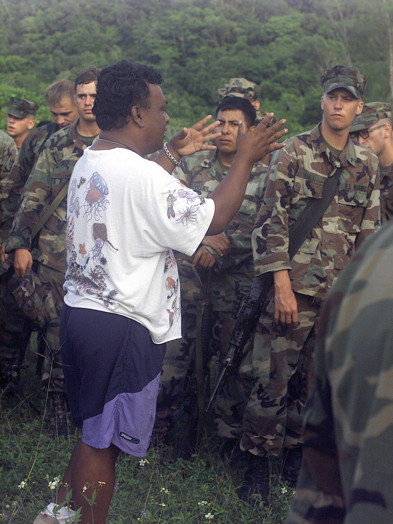 Marines from 3rd Battalion 7th Marines India Company, listen to a World War II battlefield sites tour guide on Peleliu after a simulated airfield seizure during Exercise KOA THUNDER 2001. KOA THUNDER is an exercise involving elements of 1ST Marine Air Wing (MAW), and 3rd Marine Division, where Marines conduct an Operational Readiness Exercise (ORE). The Aviation Support Element (ASE) from Kaneohe Bay, Hawaii, will be tested on command and control of several different missions, to include Tactical Recovery of Aircraft and Personal (TRAP), airfield seizures, and a Noncombatant Evacuation Operation (NEO)