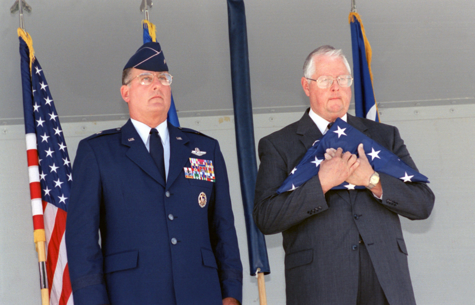 Tommy Jordan Executive Director, San Antonio - Air Logistics Center (SA-ALC) holds the last American flag to fly over Kelly AFB. Brigadier General (BGEN) Robert Murdock, USAF, SA-ALC, Commander, stands next to him. Although the closing ceremony is in history books, government officials still actually own Kelly property and will until federal and state environmental regulators okay remedies for the installation's 30 sites that need environmental clean-up, according to federal law provisions
