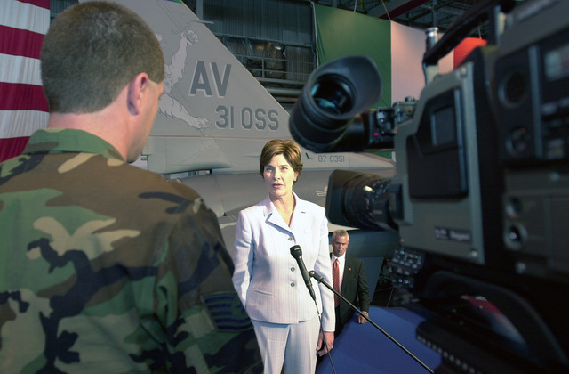 First Lady, Mrs. Laura Bush, with an F-15 Eagle as a background, is interviewed by Technical Sergeant Bobby Herron, Air Force Broadcasting Service, Aviano Air Base, Italy. On her first European visit, the First Lady of the United States visited the base to promote the Troops to Teachers program. Mrs. Laura Bush spoke to more than 500 people in Hangar One about the rewards of teaching America's children and the need for qualified teachers nationwide. Currently 4,000 former military members have become teachers through the Troops to Teachers Program